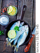 Купить «Raw fish with lemon on the pan and on a table», фото № 33787145, снято 10 июля 2020 г. (c) age Fotostock / Фотобанк Лори