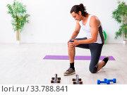 Купить «The young handsome man doing sport exercises indoors», фото № 33788841, снято 4 июня 2020 г. (c) easy Fotostock / Фотобанк Лори
