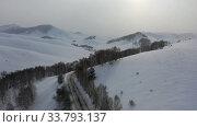 Aerial video of winter road and trees under snow in Altai. Siberia, Russia. Стоковое видео, видеограф Serg Zastavkin / Фотобанк Лори