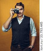 Купить «Портрет молодого привлекательного мужчины с пленочной камерой в руке», фото № 33793445, снято 18 января 2020 г. (c) Сергей Тиняков / Фотобанк Лори