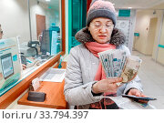 Russia, Samara, February 2017: a satisfied woman received cash in the Savings Bank of Russia. The text in Russian: Sberbank, always near, the instruction. Редакционное фото, фотограф Акиньшин Владимир / Фотобанк Лори