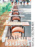 Купить «Tables with chessboard prepared for lovers on the embankment of the Volga River in a summer sunny day.», фото № 33794401, снято 12 августа 2017 г. (c) Акиньшин Владимир / Фотобанк Лори