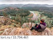 Купить «Mature man A tourist sits on a rock and looks afar to the Ural Mountains and the White River.», фото № 33794461, снято 7 сентября 2017 г. (c) Акиньшин Владимир / Фотобанк Лори