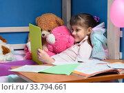 Купить «Nine-year-old girl lies on bed with toys and looks at tablet», фото № 33794661, снято 21 апреля 2020 г. (c) Иванов Алексей / Фотобанк Лори