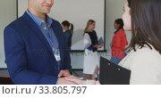 Купить «Businessman talking to businesswoman in conference room with a handsha and handshaking », видеоролик № 33805797, снято 12 октября 2019 г. (c) Wavebreak Media / Фотобанк Лори