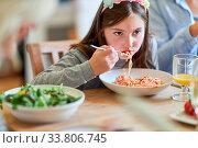 Hungriges Kind beim Spaghetti essen mit Tomatensauce beim Abendessen. Стоковое фото, фотограф Zoonar.com/Robert Kneschke / age Fotostock / Фотобанк Лори