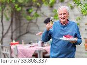 Купить «Senior feiert Geburtstag im Garten im Sommer mit Kuchen und einem Glas Sekt», фото № 33808337, снято 25 мая 2020 г. (c) age Fotostock / Фотобанк Лори