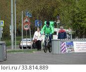 """Купить «Курьер сервиса быстрой доставки еды """"Delivery Club"""" едет на велосипеде по Хабаровской улице в дни самоизоляции при коронавирусе COVID-19. Район Гольяново. Город Москва», эксклюзивное фото № 33814889, снято 5 мая 2020 г. (c) lana1501 / Фотобанк Лори"""