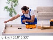Купить «Young male contractor installing furniture at home», фото № 33815537, снято 11 ноября 2019 г. (c) Elnur / Фотобанк Лори