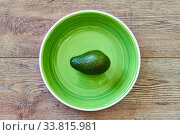 Green avocado on a green plate on a wooden tabletop. Стоковое фото, фотограф Евгений Харитонов / Фотобанк Лори