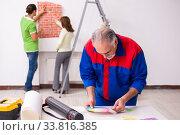 Купить «Young couple and old contractor in home renovation concept», фото № 33816385, снято 2 сентября 2019 г. (c) Elnur / Фотобанк Лори