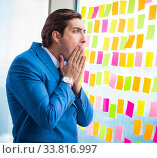 Купить «Young handsome employee with many conflicting priorities», фото № 33816997, снято 15 августа 2018 г. (c) Elnur / Фотобанк Лори