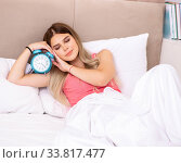 Купить «Young woman waking up in the morning in bed», фото № 33817477, снято 29 июня 2018 г. (c) Elnur / Фотобанк Лори