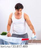 Купить «Young man ironing in the bedroom», фото № 33817489, снято 27 июня 2018 г. (c) Elnur / Фотобанк Лори