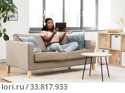Купить «woman with tablet pc listening to music at home», фото № 33817933, снято 3 мая 2020 г. (c) Syda Productions / Фотобанк Лори