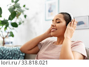 Купить «woman in headphones listening to music at home», фото № 33818021, снято 25 марта 2020 г. (c) Syda Productions / Фотобанк Лори