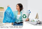 Купить «smiling woman sorting plastic waste and trash bag», фото № 33818337, снято 18 апреля 2020 г. (c) Syda Productions / Фотобанк Лори