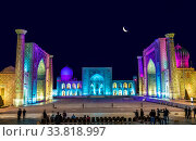 A few tourists on Registan square in Samarkand with Ulugbek madrasah, Sherdor madrasah and Tillya-Kari madrasah at moon night with multicolored backlight. Uzbekistan (2019 год). Редакционное фото, фотограф Наталья Волкова / Фотобанк Лори