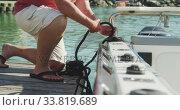 Купить «Side view low section of a Caucasian man untying a rope on the boat harbor side», видеоролик № 33819689, снято 4 февраля 2020 г. (c) Wavebreak Media / Фотобанк Лори