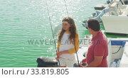 Купить «Side view of a Caucasian man and his teenage daughter holding fishing rods», видеоролик № 33819805, снято 4 февраля 2020 г. (c) Wavebreak Media / Фотобанк Лори