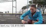 Купить «Sporty Caucasian woman exercising in an outdoor gym during daytime», видеоролик № 33819985, снято 8 августа 2019 г. (c) Wavebreak Media / Фотобанк Лори