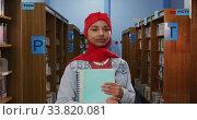 Купить «Portrait of a smiling Asian female student wearing a red hijab studying in a library», видеоролик № 33820081, снято 7 июня 2019 г. (c) Wavebreak Media / Фотобанк Лори