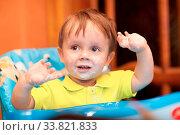 Купить «Happy little boy wearing yellow t-shirt and looking aside smiles at home, face got dirty with yoghurt, he gesticulates», фото № 33821833, снято 7 июня 2020 г. (c) age Fotostock / Фотобанк Лори