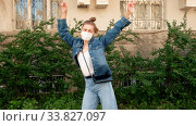 Купить «Delighted female in casual outfit and disposable surgical mask dancing on city street with outstretched arms and closed eyes during corona virus pandemic», видеоролик № 33827097, снято 14 мая 2020 г. (c) Ekaterina Demidova / Фотобанк Лори