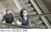 Focused people in medical masks and rubber gloves lifting on escalator keeping distance to prevent spread of COVID 19 virus. Стоковое видео, видеограф Яков Филимонов / Фотобанк Лори