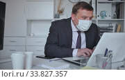 Focused businessman in disposable face mask working on laptop in office. Necessary precautions during COVID 19 pandemic. Стоковое видео, видеограф Яков Филимонов / Фотобанк Лори