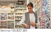 Купить «Skillful young seamstress looking for buttons for sewing clothes in haberdasher shop», видеоролик № 33827361, снято 23 мая 2020 г. (c) Яков Филимонов / Фотобанк Лори