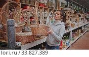 Female customer choosing wicker products in home decor warehouse. Стоковое видео, видеограф Яков Филимонов / Фотобанк Лори