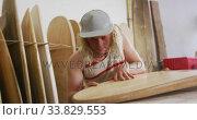 Caucasian male surfboard maker checking one of the surfboards in his studio. Стоковое видео, агентство Wavebreak Media / Фотобанк Лори