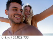 Купить «Caucasian couple enjoying time at the beach», фото № 33829733, снято 25 февраля 2020 г. (c) Wavebreak Media / Фотобанк Лори