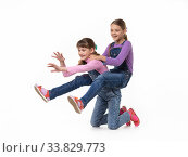 Hilarious girl rides on herself riding her sister on a white background. Стоковое фото, фотограф Иванов Алексей / Фотобанк Лори