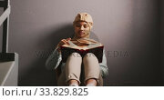 Asian female student wearing a beige hijab sitting on a staircase and reading a book. Стоковое видео, агентство Wavebreak Media / Фотобанк Лори