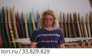 Caucasian male surfboard maker in his studio with surfboards in a rack in background. Стоковое видео, агентство Wavebreak Media / Фотобанк Лори