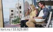 Купить «Two Caucasian male surfboard makers sitting on a bench and drinking takeaway coffee», видеоролик № 33829881, снято 6 марта 2020 г. (c) Wavebreak Media / Фотобанк Лори