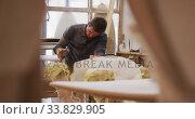 Купить «Caucasian male surfboard maker working in his studio and making a wooden surfboard», видеоролик № 33829905, снято 6 марта 2020 г. (c) Wavebreak Media / Фотобанк Лори