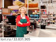 Купить «Frau als Kassiererin oder Verkäuferin steht mit verschränkten Armen an der Kasse», фото № 33831905, снято 5 июня 2020 г. (c) age Fotostock / Фотобанк Лори