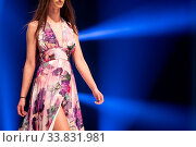 Female model walks the runway in a beautiful colorful pink summer dress during a Fashion Show. Fashion catwalk event showing new collection of clothes. Blue background. Unrecognizable person. Стоковое фото, фотограф Zoonar.com/Cylonphoto / age Fotostock / Фотобанк Лори