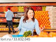 Купить «Junge Frau als Kundin beim bio Tomaten einkaufen in der Gemüseabteilung», фото № 33832045, снято 5 июня 2020 г. (c) age Fotostock / Фотобанк Лори