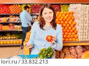Купить «Junge Frau hält eine gesunde Bio Tomate in der Hand in der Gemüseabteilung», фото № 33832213, снято 5 июня 2020 г. (c) age Fotostock / Фотобанк Лори
