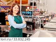 Купить «Frau in grüner Schürze als Kassiererin an der Kasse im Supermarkt oder Discounter», фото № 33832245, снято 5 июня 2020 г. (c) age Fotostock / Фотобанк Лори