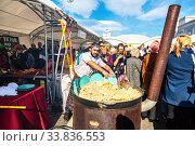 Купить «Cooking appetizing traditional oriental pilaf in a large cauldron», фото № 33836553, снято 5 октября 2019 г. (c) FotograFF / Фотобанк Лори