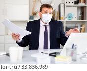 Купить «Dissatisfied man in protective mask working at office», фото № 33836989, снято 2 июня 2020 г. (c) Яков Филимонов / Фотобанк Лори