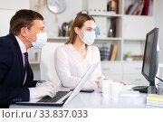 Entrepreneur in medical mask working with female coworker in office. Стоковое фото, фотограф Яков Филимонов / Фотобанк Лори