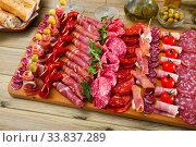 Slicing sausages fuet, ham, salami, chorizo with cherry tomatoes and olives. Стоковое фото, фотограф Яков Филимонов / Фотобанк Лори