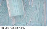 Купить «Slow motion flying medical face masks. Close-up view of fall lot blue surgical disposable respirator bandage for human», видеоролик № 33837549, снято 12 мая 2020 г. (c) А. А. Пирагис / Фотобанк Лори