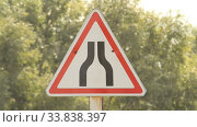 Купить «Road narrowing road sign near a road against a background of trees. Summer», видеоролик № 33838397, снято 24 мая 2020 г. (c) Mikhail Erguine / Фотобанк Лори